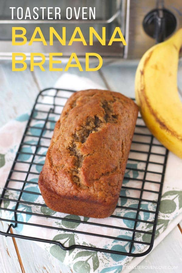 A mini loaf of banana bread cooling on a rack in front of a toaster oven