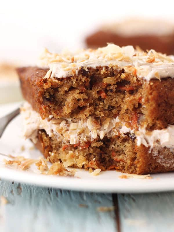 Closeup of a slice of carrot cake showing moist crumb and bits of carrot throughout.