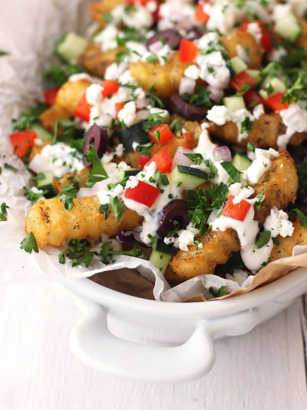 Loaded fries in a white dish.