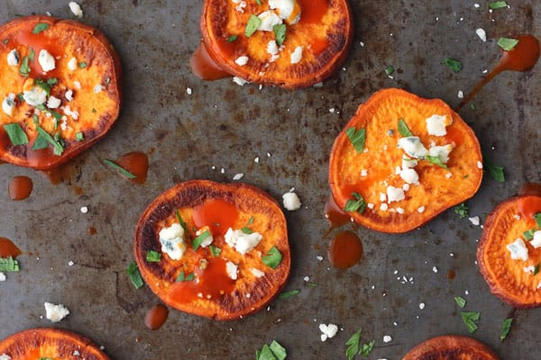 Sheet pan of roasted sweet potato slices topped with blue cheese and buffalo sauce.