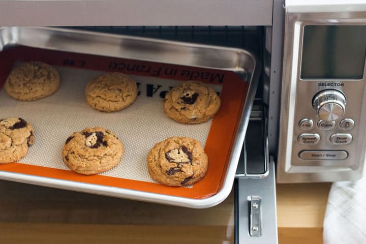 A baking sheet of cookies inside of a toaster oven.