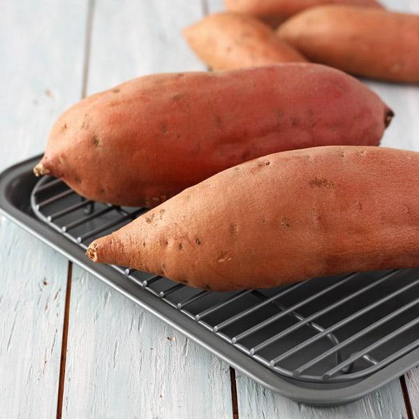 Raw sweet potatoes on pan
