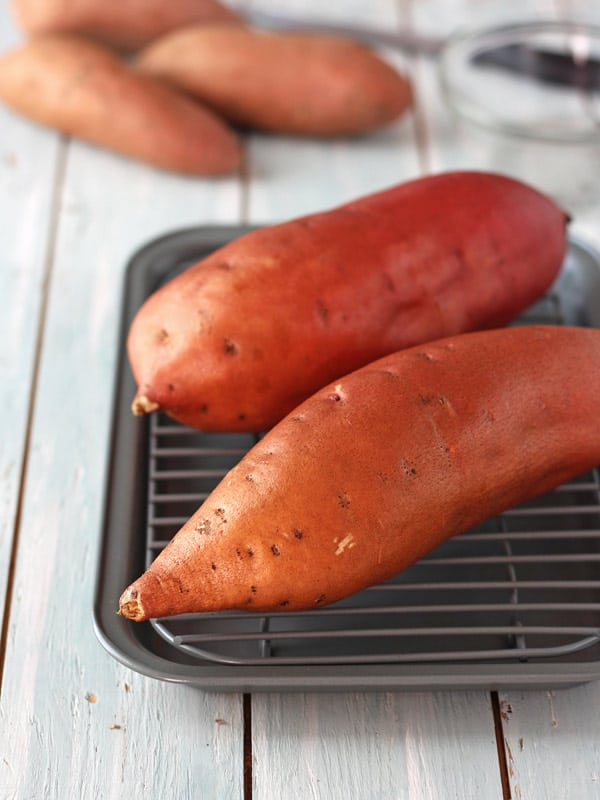 Two sweet potatoes oiled on a pan