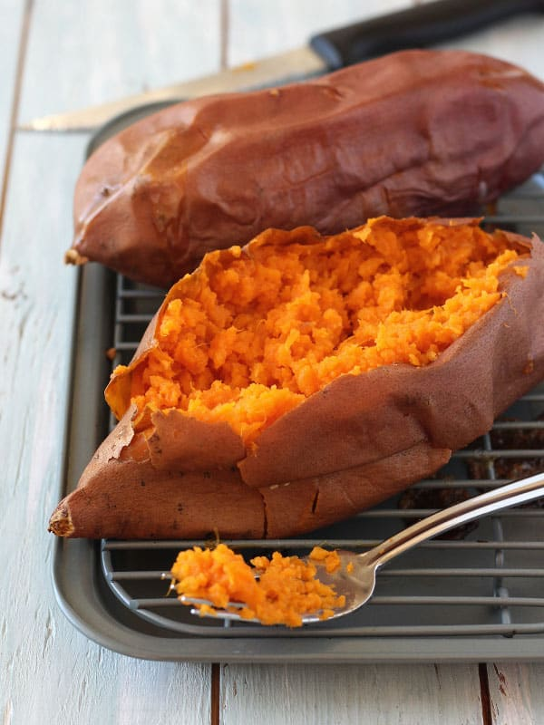 Baked sweet potato on pan sliced open with fluffy orange inside exposed