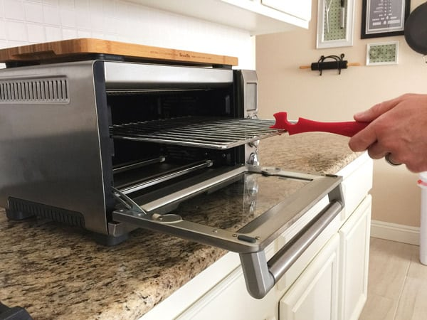 hand holding a red silicone push/pull to pull rack out of a toaster oven