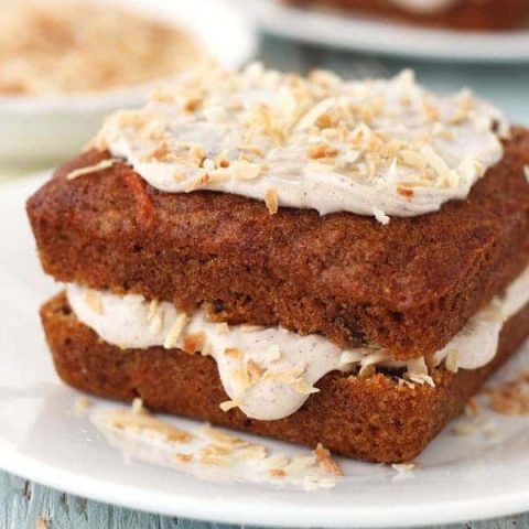 Mini square carrot cakes topped with frosting and toasted coconut.