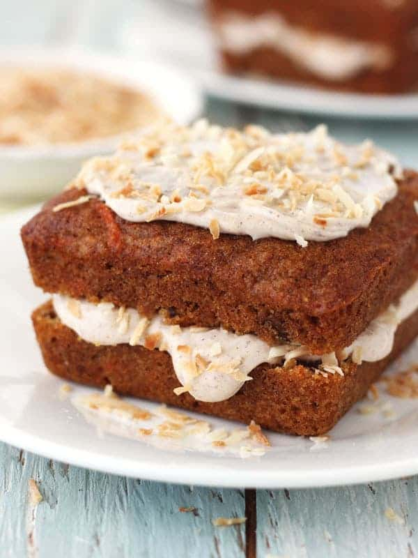 Mini carrot cake loaded with frosting and topped with toasted coconut.