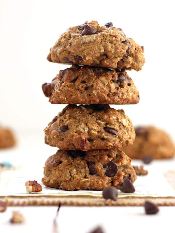A stack of four chocolate chips cookies surrounded by nuts and chocolate chips.