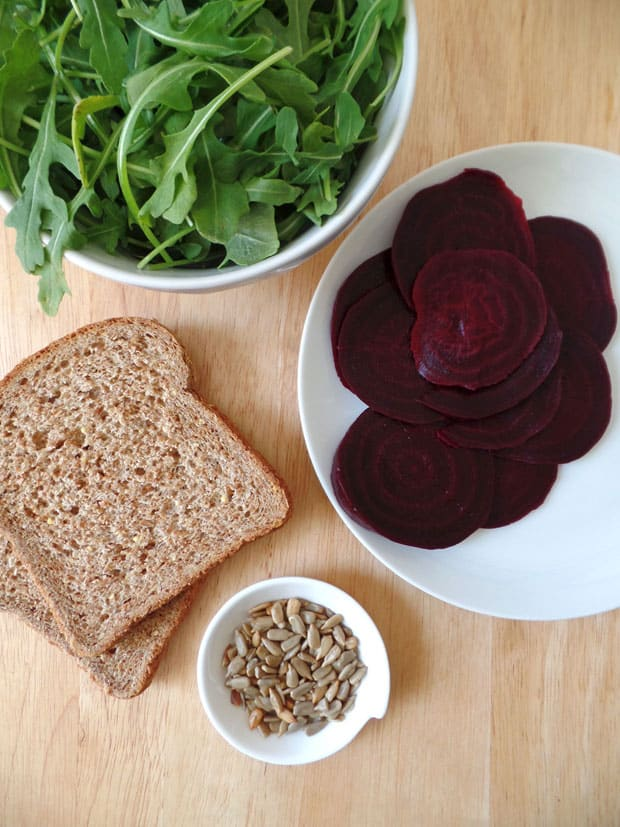Bread, sliced beets, arugula, and sunflower seeds on a cutting board.
