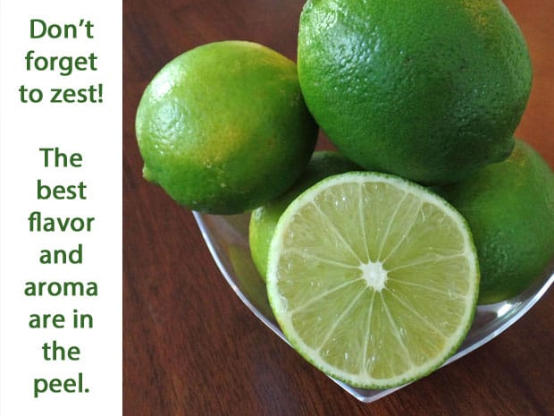 Limes in a clear bowl on a wooden table.