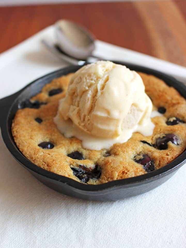 A mini skillet cookie with a scoop of ice cream melting on top on a white napkin with two spoons.