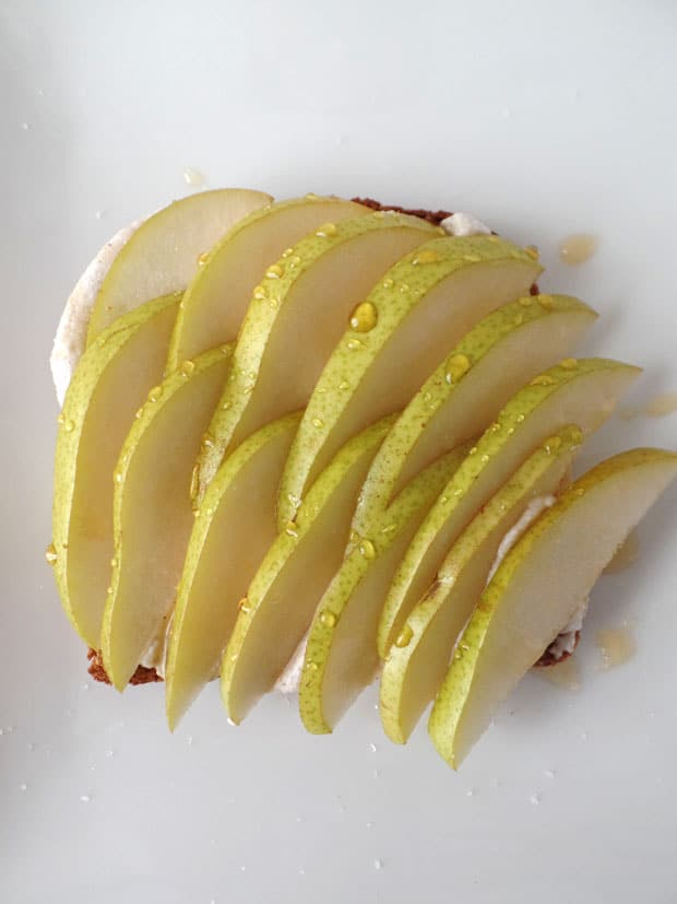 Ginger Ricotta Pear Toast, crispy whole grain toast smothered with spicy cinnamon ginger ricotta and topped with juicy pear slices and a drizzle of honey.