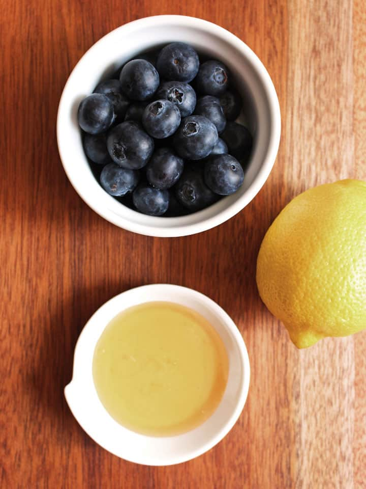White bowls with blueberries, honey and a lemon a wooden table.