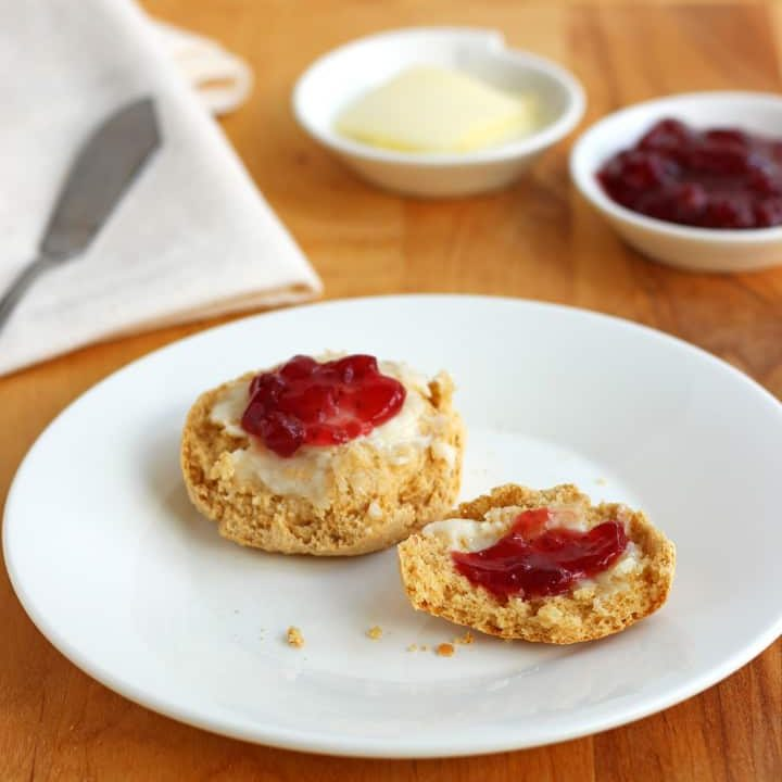 Split biscuit topped with butter and jam.