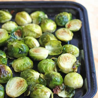 Roasted Brussels sprouts on a small black pan.