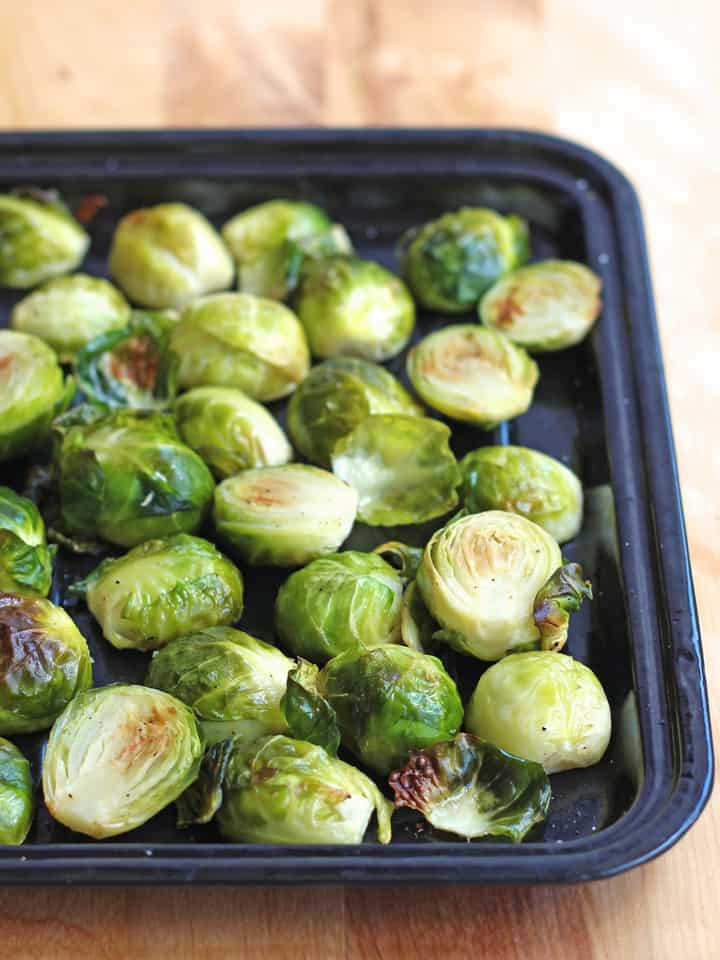 Roasted Brussels Sprouts on a black toaster oven baking sheet.
