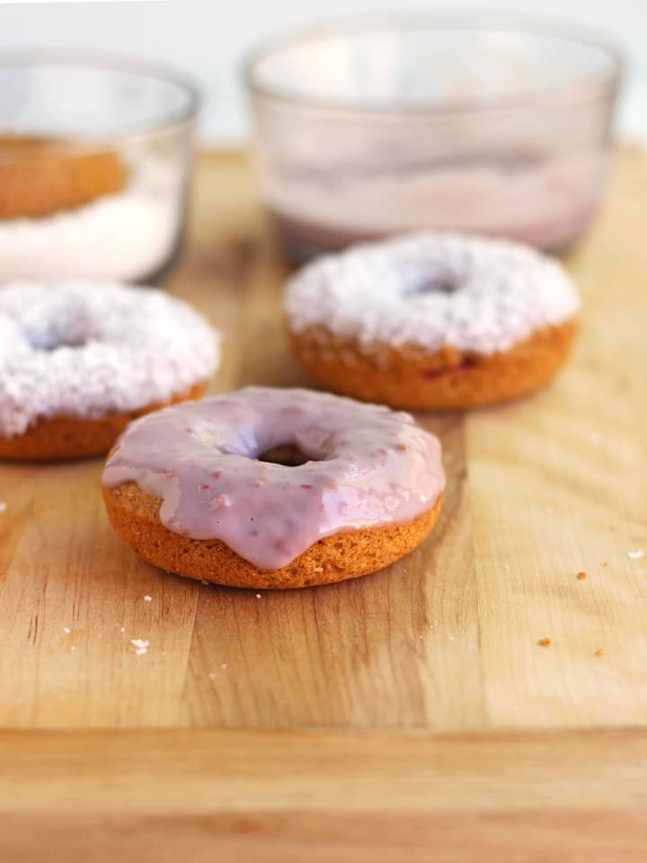 Donuts with raspberry glaze on a wooden cutting board.