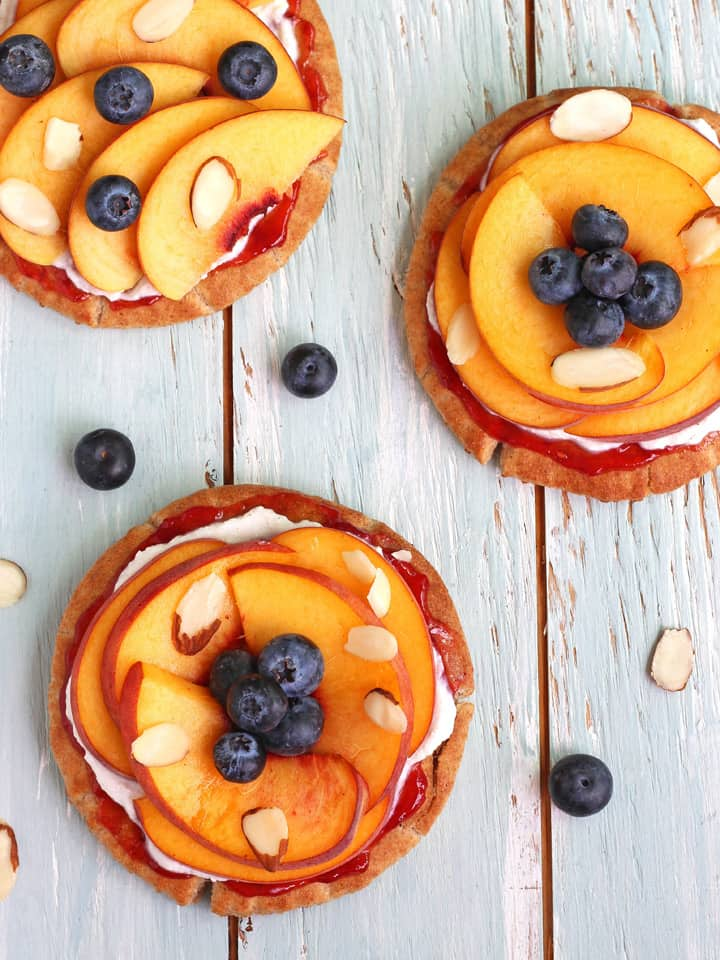 These Peachy Pita Breakfast Pizzas are a quick and healthy toaster oven recipe that is super kid-friendly. Toast up a few mini pitas and let the kids make their own pizzas with a little sweet raspberry preserves, ricotta cheese, sliced peaches and fresh blueberries.
