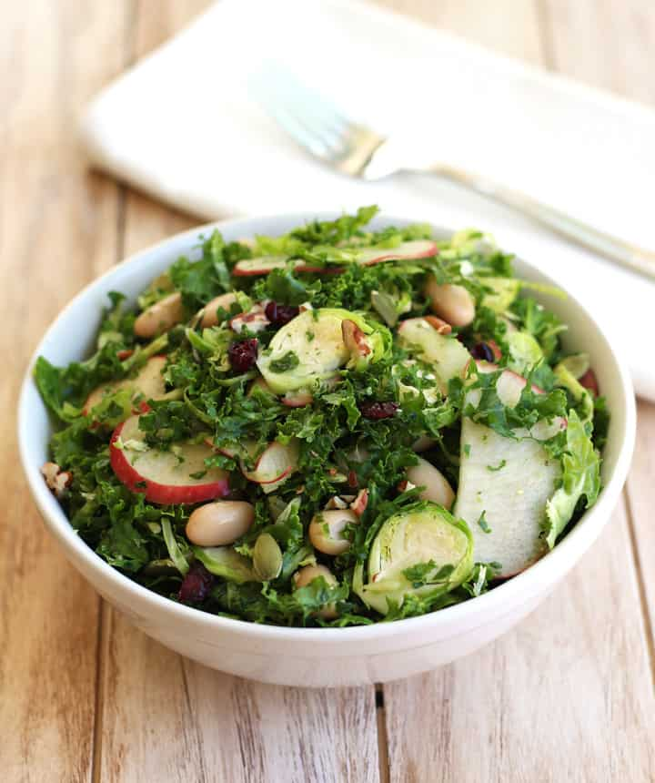 Quick Kale Apple Salad. Easily create a healthy chopped salad using your food processor. Enjoy a delicious salad full of kale, Brussels sprouts, apples, cranberries, nuts and seeds all topped with a spicy Sriracha Vinaigrette.