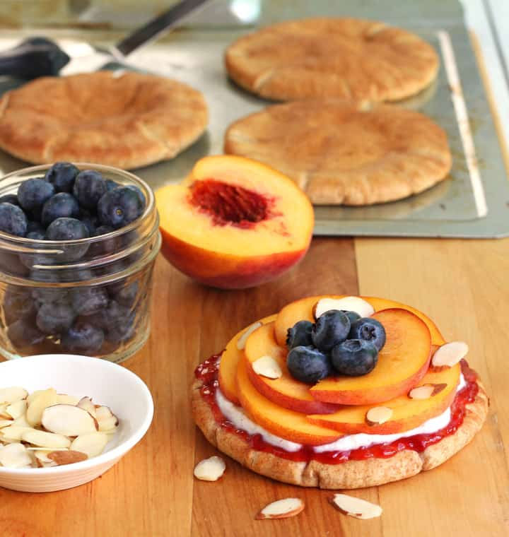 Peachy Pita Breakfast Pizzas are a delicious and seasonal summer breakfast. Whole grain pitas topped with ricotta, fresh peaches and blueberries. A single serving of two filling pizzas is less than 400 calories!