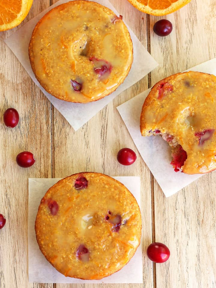 Overhead view of baked donuts surrounded by whole fresh cranberries.