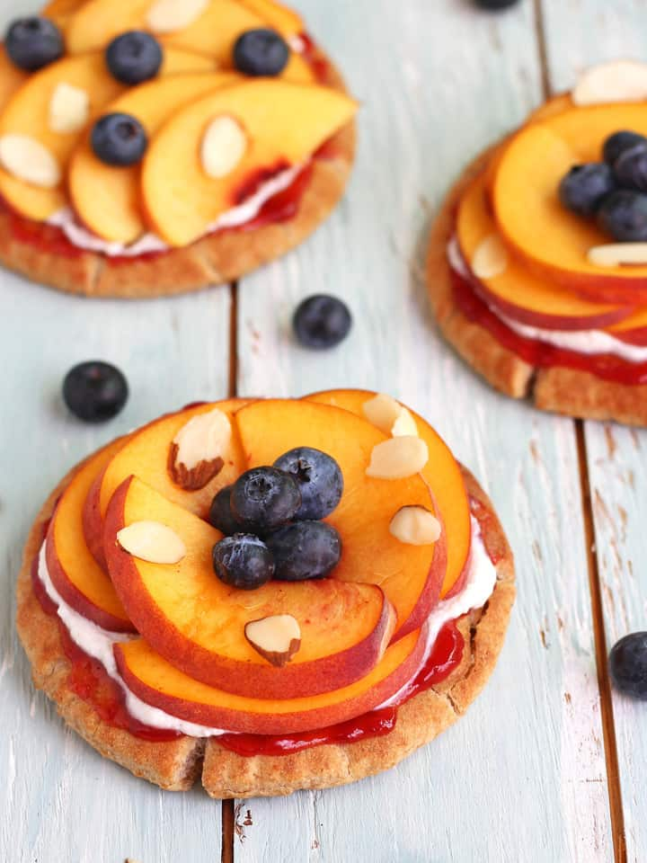 Peachy Pita Breakfast Pizzas. Whole grain mini pitas topped with juicy sweet peaches, raspberry preserves, lemony ricotta cheese and fresh blueberries. Less than 15 minutes for this easy healthy toaster oven breakfast.