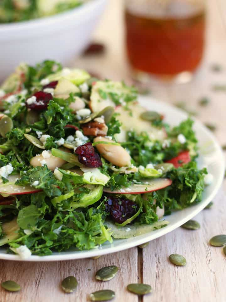 Quick Kale Apple Salad. Kale, Brussels sprouts, apples, cranberries, nuts and seeds all dressed with a spicy Sriracha Vinaigrette. Makes two large and filling salads perfect for a quick and healthy lunch or dinner!