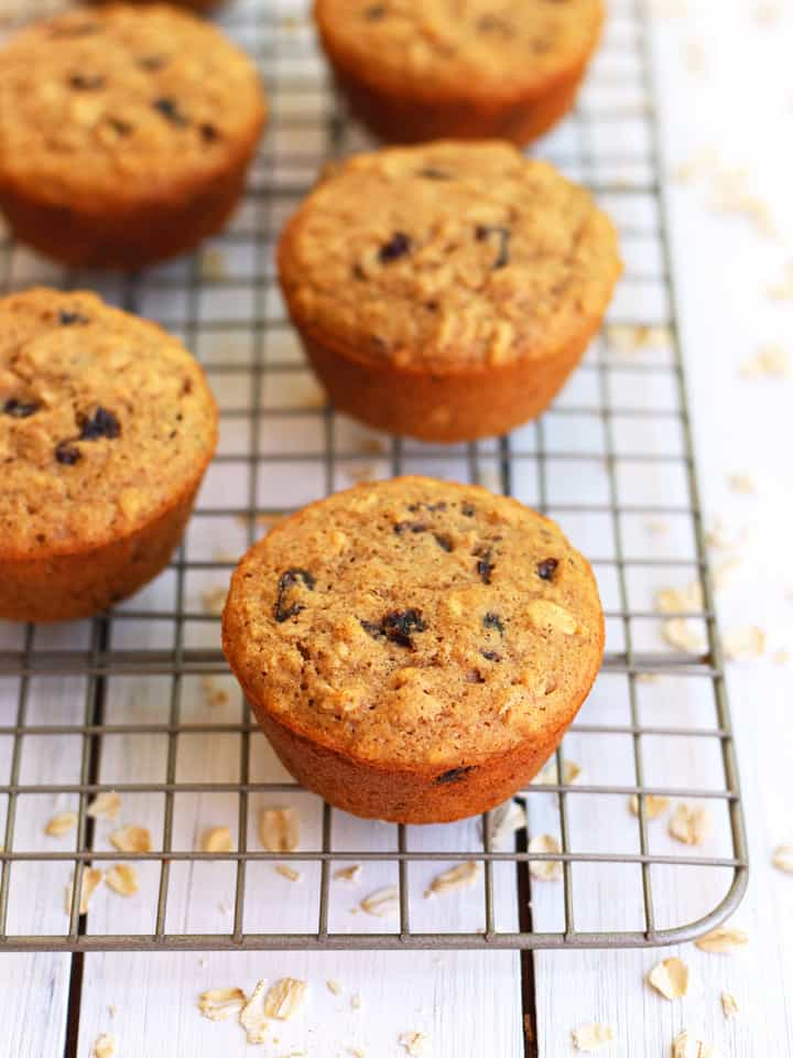 Toaster Oven Oatmeal Raisin Muffins on a metal cooling rack with oats scattered underneath.