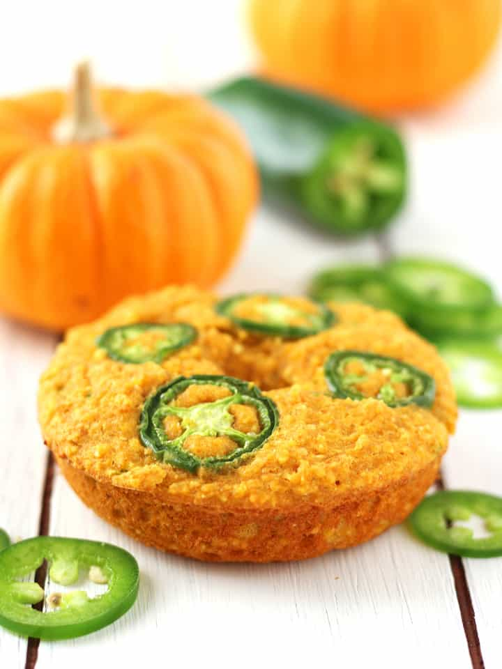 Jalapeño Pumpkin Cornbread Donuts on a white wooden table with mini pumpkins and jalapeño slices.