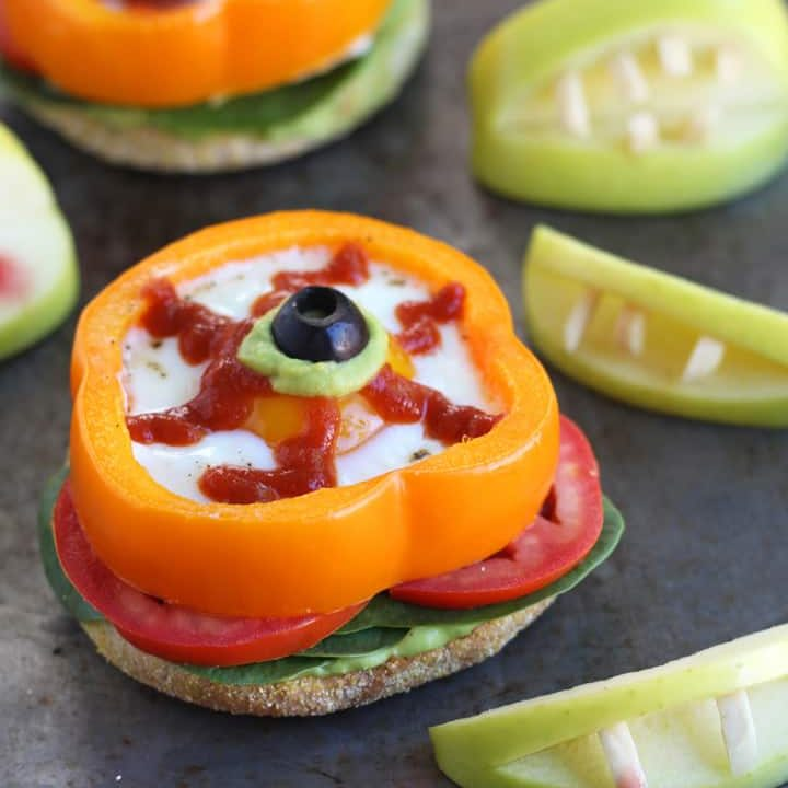 Eggs baked in orange bell pepper slices next to apples with almond 'vampire' teeth.