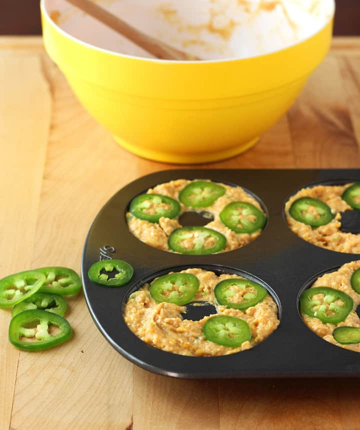 Jalapeño Pumpkin Cornbread spooned into a donut pan and topped with jalapeno slices.