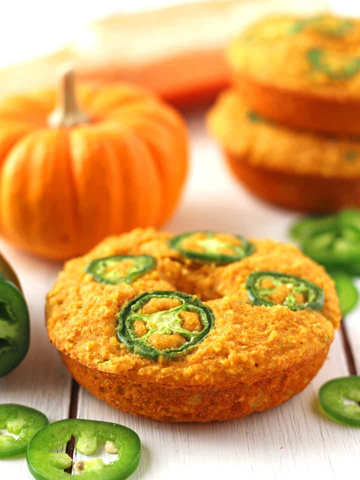 Jalapeño Pumpkin Cornbread Donuts on a white table with a mini pumpkin and jalapeño slices.