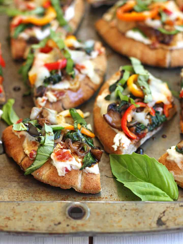 Veggie Pita Pizza Bites. Little slices of yum that start with warm mini pitas smothered creamy ricotta and sun-dried tomatoes. Piled high with sautéed mushrooms and spinach, crisp mini bell pepper slices and a tiny bit of melted mozzarella. A sprinkling of thinly sliced fresh basil and drizzle of balsamic vinegar finish off this tasty vegetarian appetizer.
