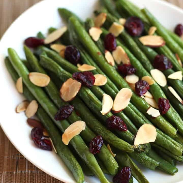 A plate of green beans topped with dried cranberries and toasted almond slices.