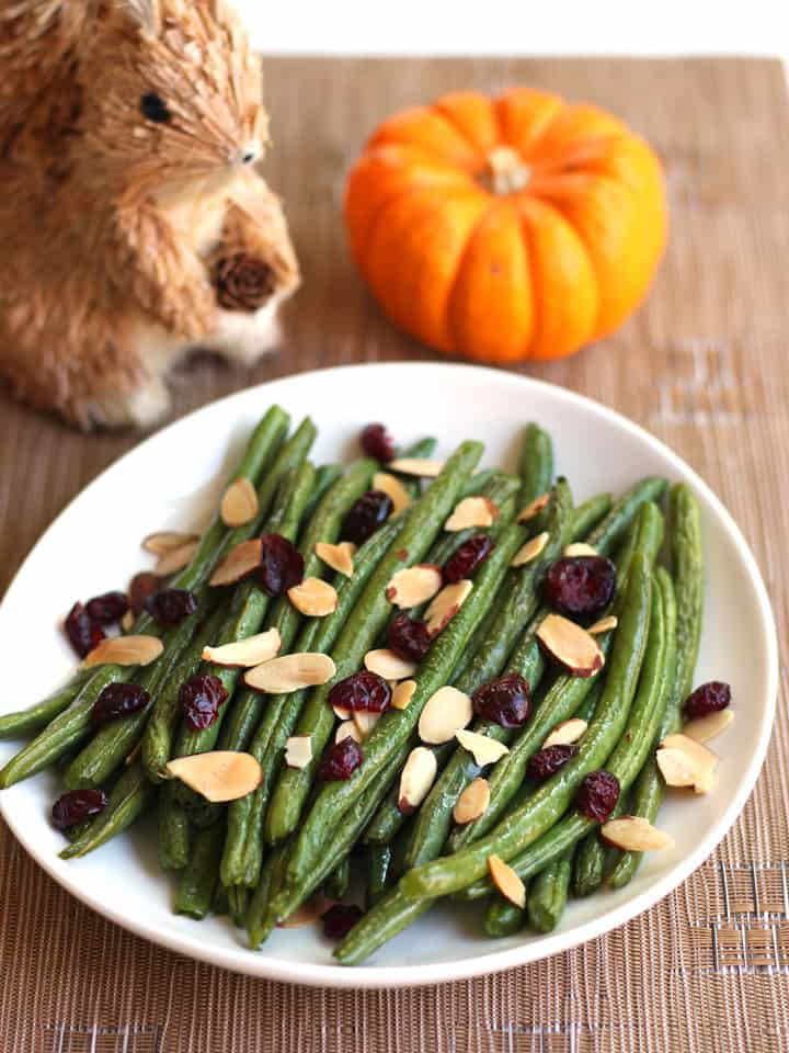 Table with plate of green beans, mini pumpkin and a squirrel.