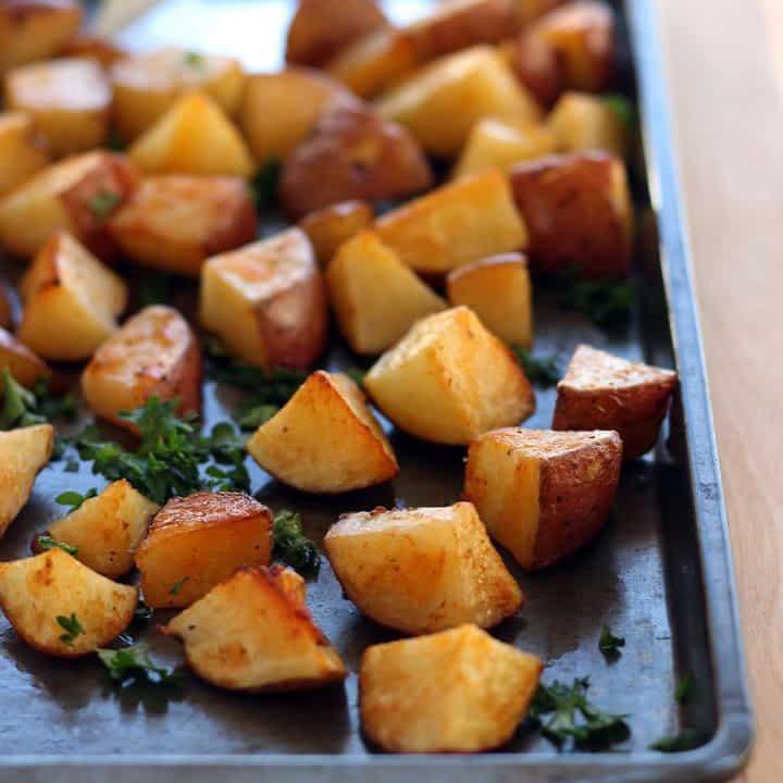 Roasted potato cubes on a dark sheet pan.