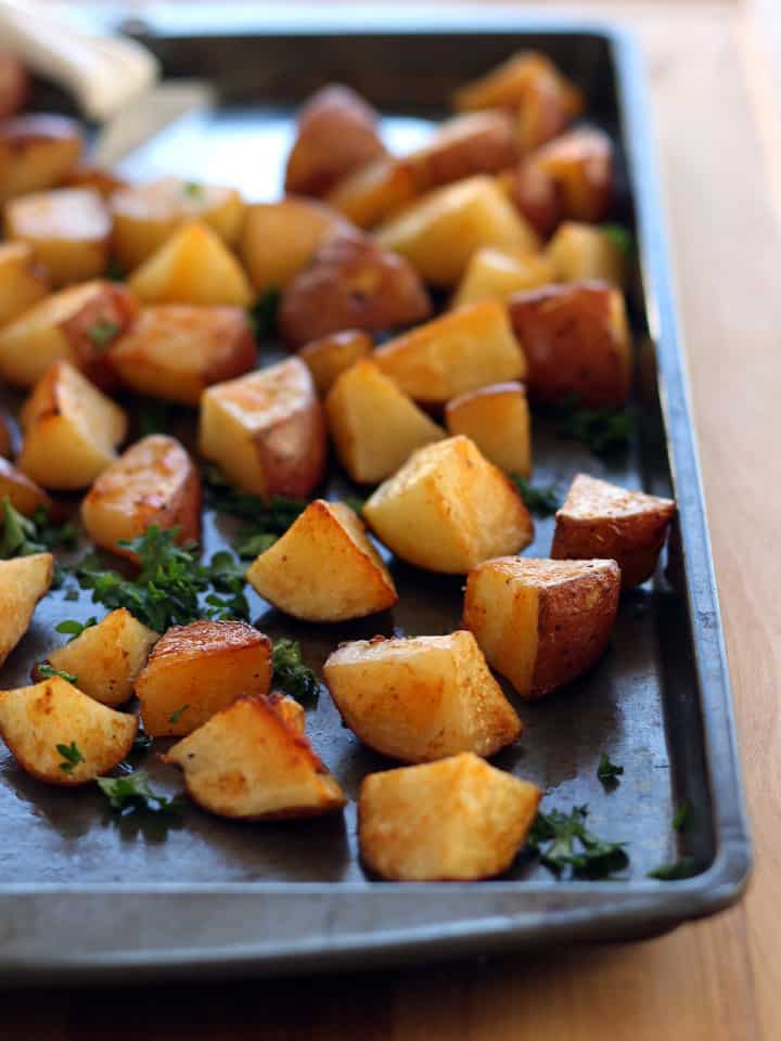 Roasted potato cubes on a sheet pan with a spatula.
