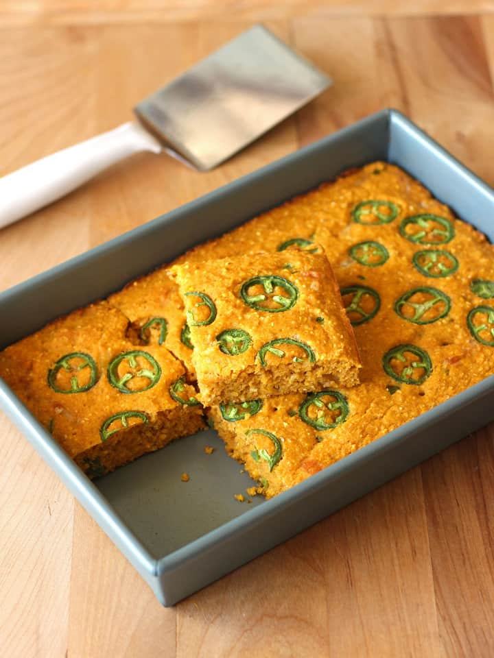 Jalapeño Pumpkin Cornbread in an 11 x 7 metal pan on a cutting board.