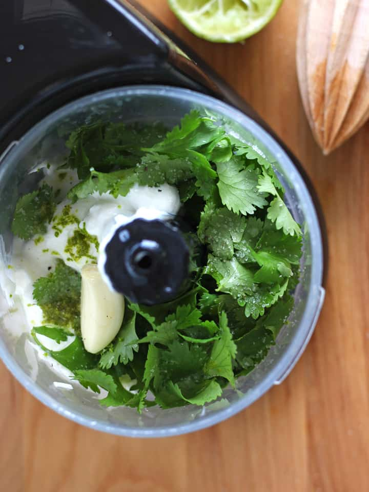 Overhead photo of a mini food processor filled with cilantro and garlic.