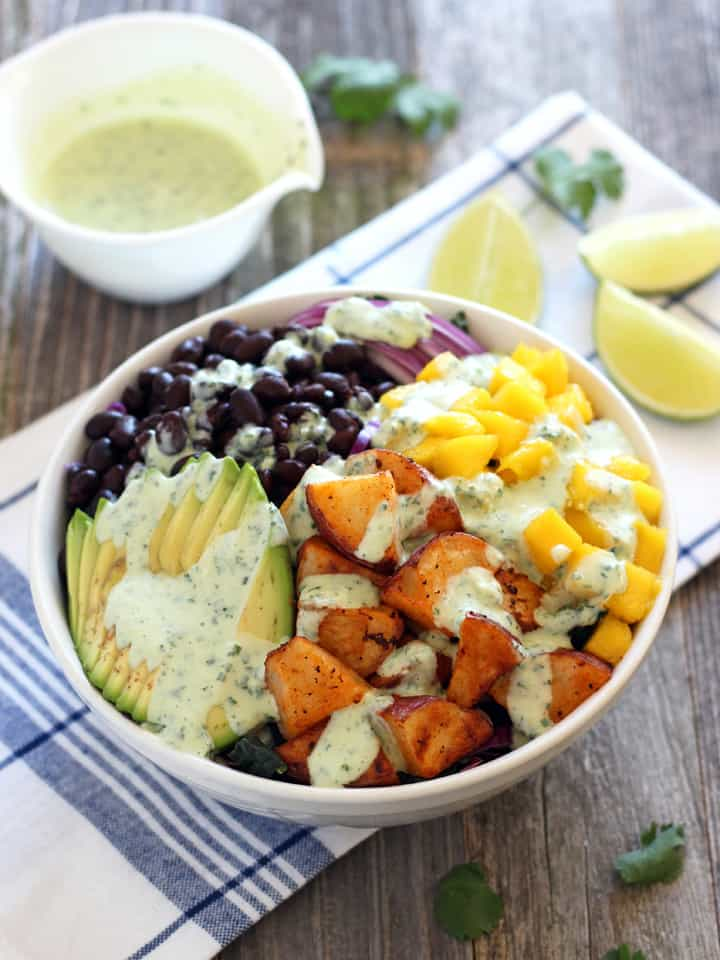A white bowl filled with avocado, roasted potatoes, mango, and black beans drizzled with dressing.
