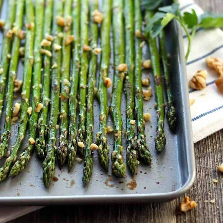 Roasted asparagus spears on a small sheet pan.