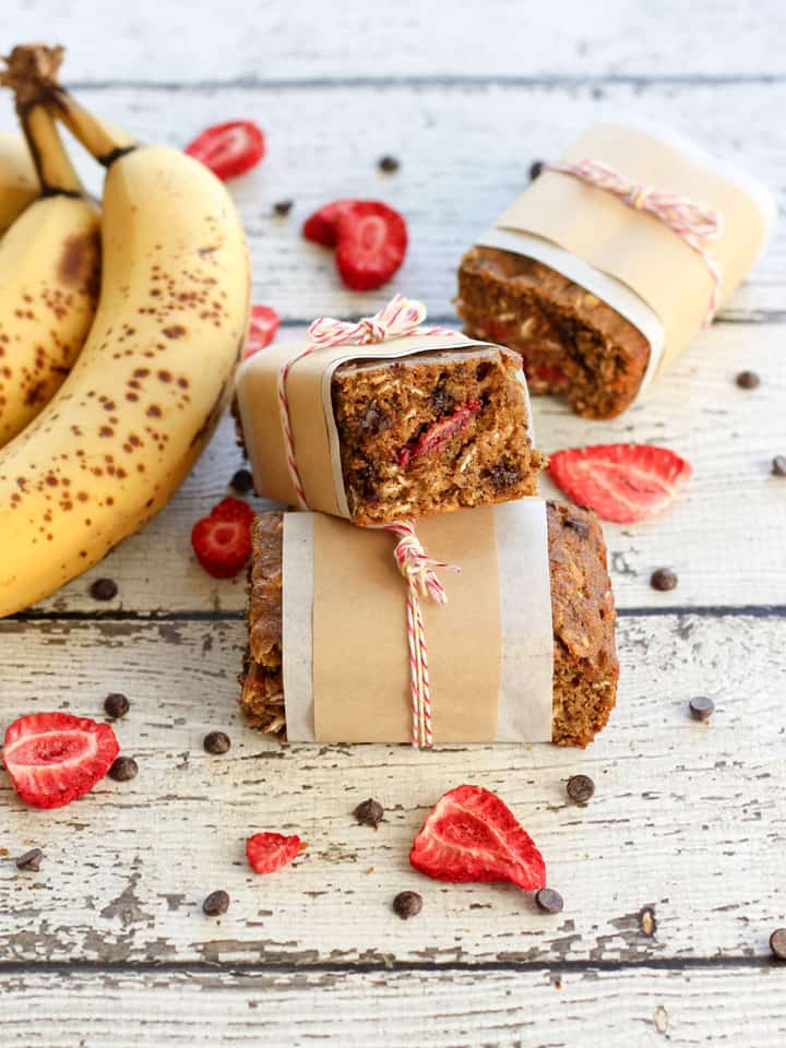 Stacked snack bars next to bananas, freeze dried strawberries, and mini chocolate chips.