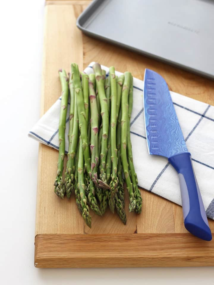 Bunch of fresh asparagus on a cutting board with a knife.