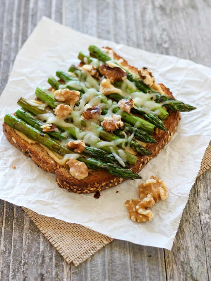 Balsamic Asparagus and Hummus Toast. Garlicy hummus spread across whole grain toast topped with roasted asparagus, melted cheese, walnuts and a drizzle of balsamic vinegar. Make it a sandwich with an extra slice of toasted bread.