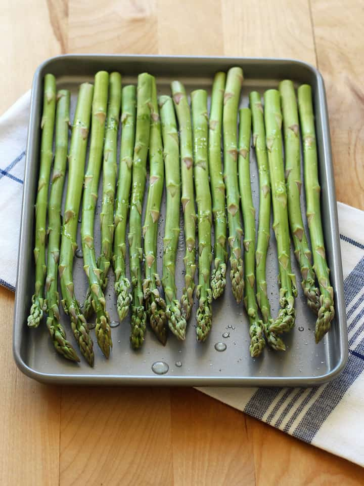 Asparagus spears on a toaster oven baking sheet drizzled with oil.