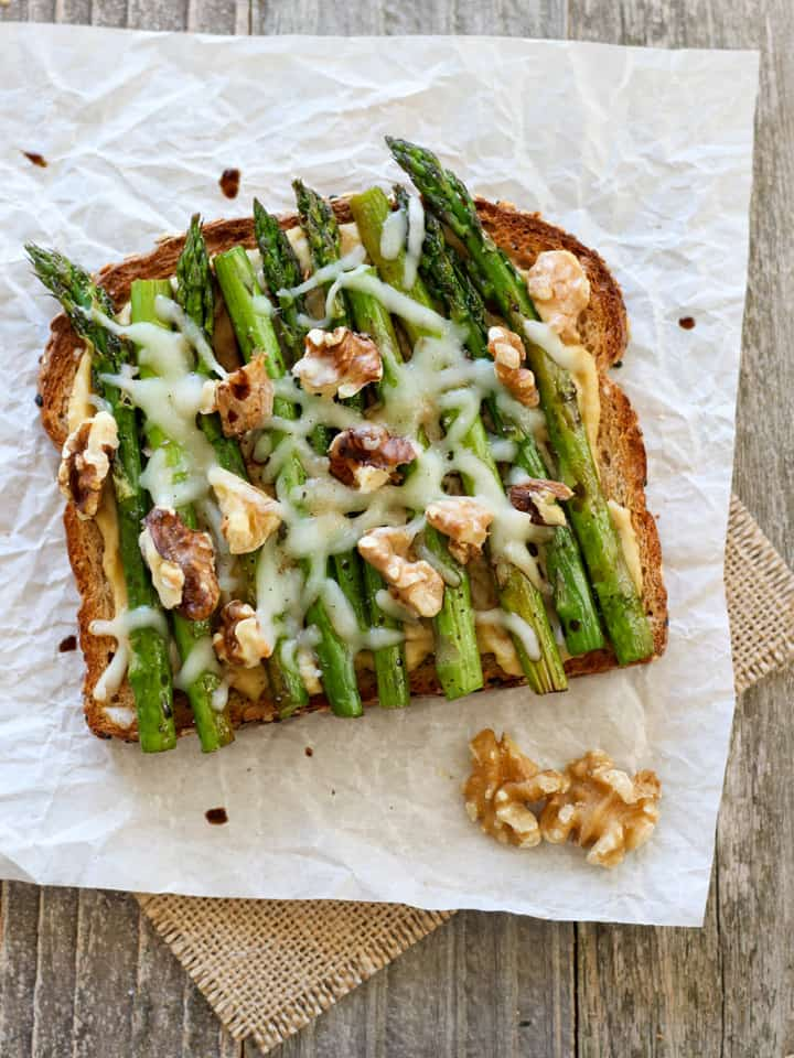 Balsamic Asparagus and Hummus Toast. Whole grain toast topped with hummus, roasted asparagus, melted cheese, walnuts and a drizzle of balsamic vinegar.