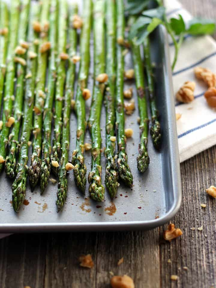 Asparagus spears on a mini baking sheet topped with copped walnuts and balsamic vinegar.