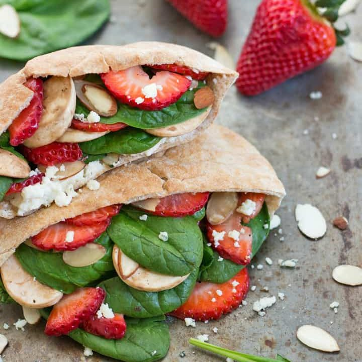 Sheet pan with stuffed pita pockets, strawberries, and spinach.