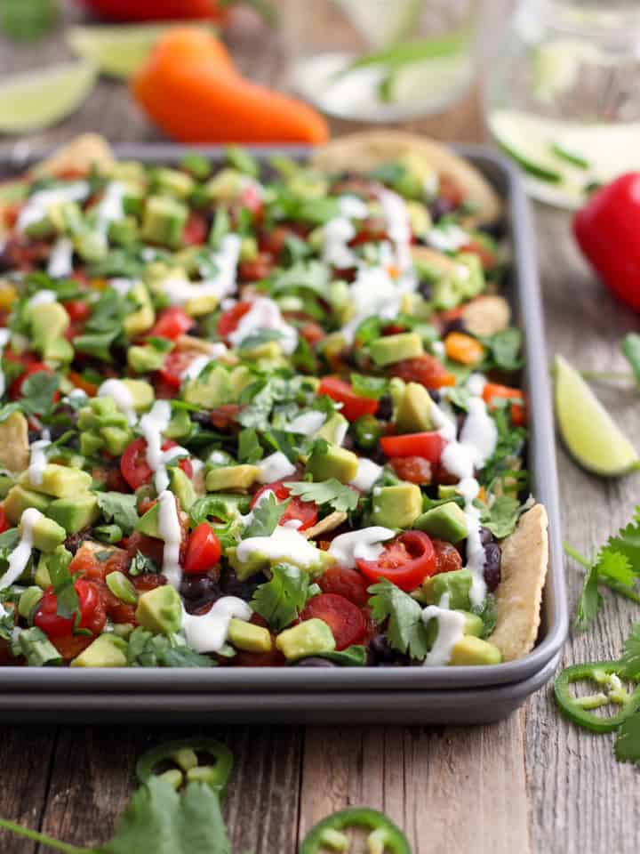 A small pan of veggie nachos on a table with mini peppers and jalapeno slices.