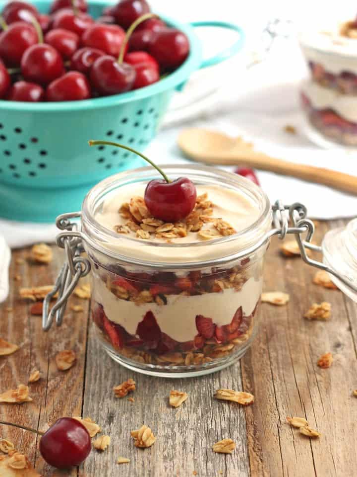 A small mason jar layered with yogurt, granola, and fresh cherries.